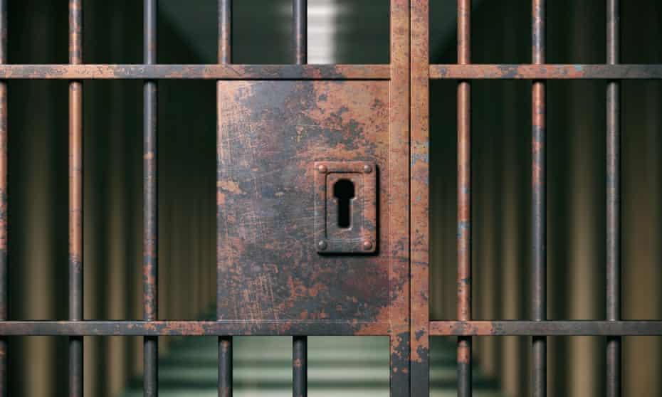 Prison interior. Locked rusty door closeup, dark jail background