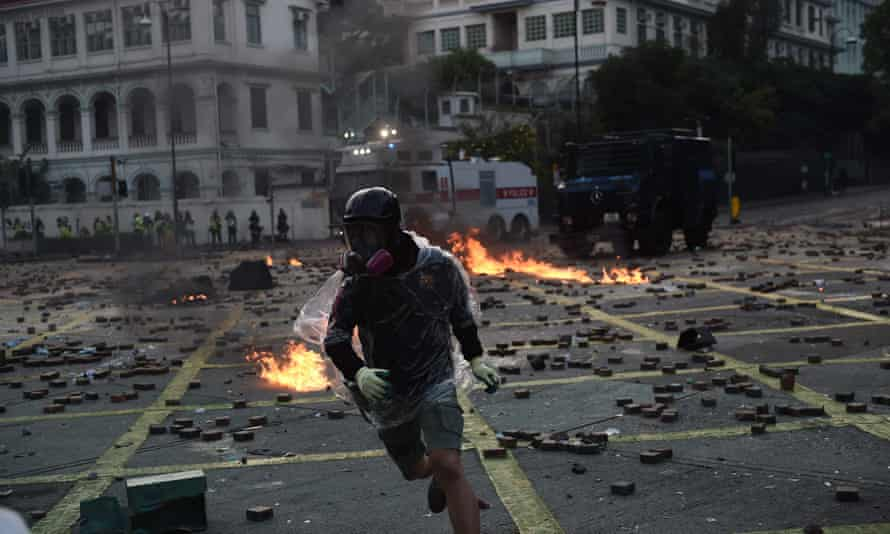 A protester runs after throwing a Molotov cocktail at the police outside Hong Kong Polytechnic University in Hong Kong, November 2019.