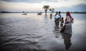Flood victims try to reach safe zones after their homes submerged under the flood water in Jalapur Bhattian, Pakistan.