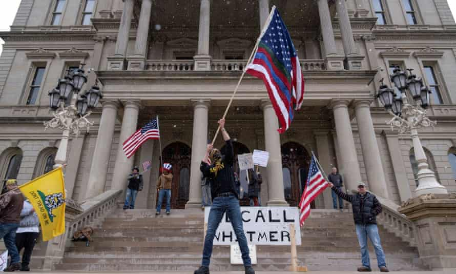 People hold flags and placards as hundreds of supporters of the Michigan Conservative Coalition protest against the stay-at-home order.