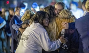 People hug each other during a vigil for the shooting victims in Santa Clarita.