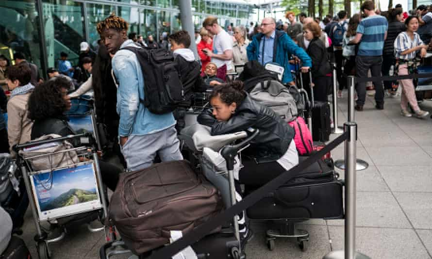 People queue with their luggage outside Heathrow Terminal 5 on Sunday.