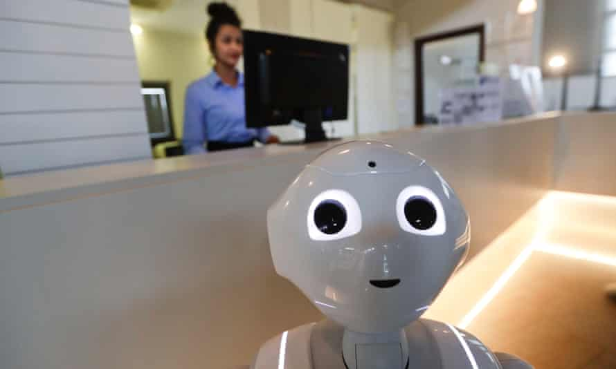 A robot works alongside a woman at the front desk of a hotel in Peschiera del Garda, Italy.