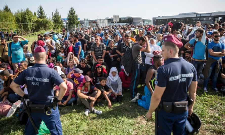 Hungarian police monitor a large group of migrants and refugees at a border crossing between Hungary and Croatia at Beremend.
