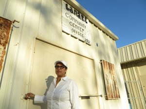 Isabel Solorio stands next to the defunct water treatment plant across from her home in Lanare.