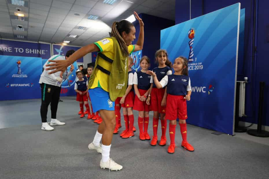 Marta of Brazil high fives match mascots in the tunnel ahead of a group C match between Brazil and Jamaica at Stade des Alpes.