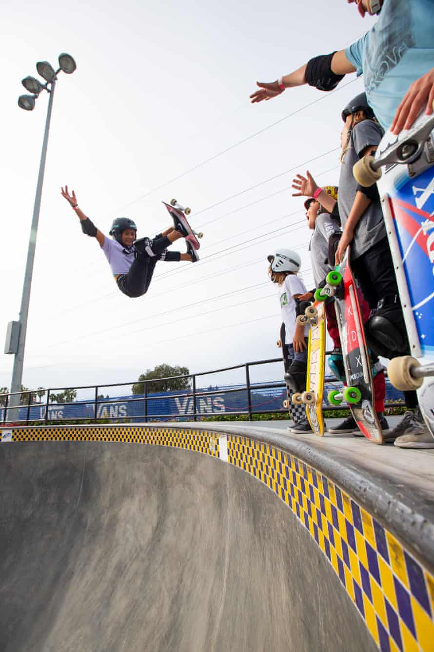 Sky performs a frontside grab as young skaters watch from the rim.