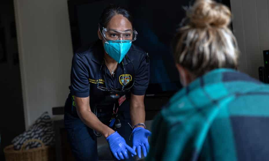 A Houston fire department EMS senior supervisor speaks with a woman who has Covid before transporting her to a hospital.