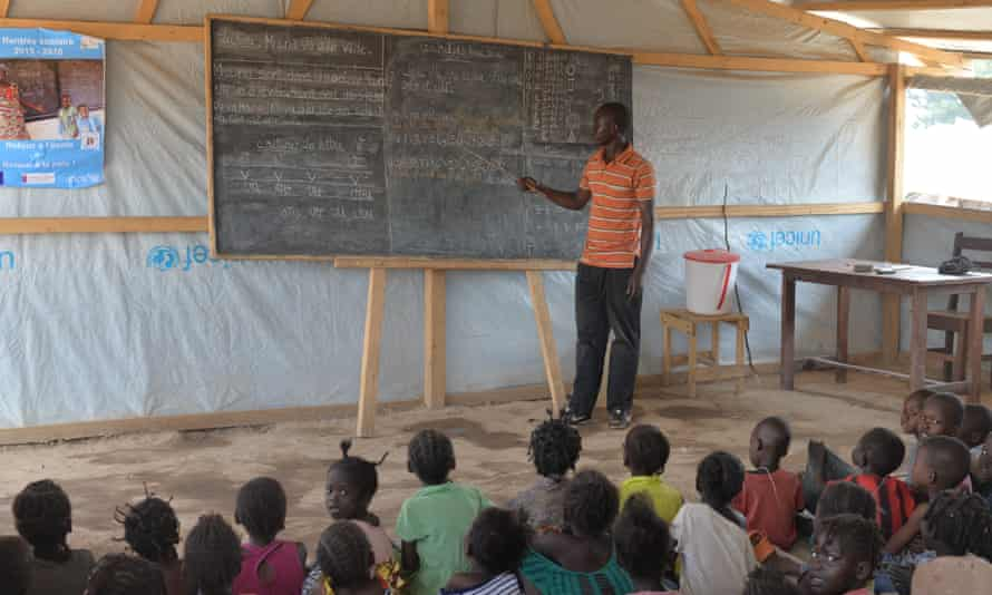 A lesson in a Unicef-funded temporary school in Bangui, Central African Republic. The blue poster reads 'Return to school: return to peace'.