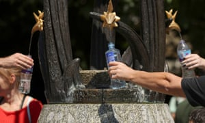 People fill up their bottles from a water fountain in Green Park, London, during the hot weather.
