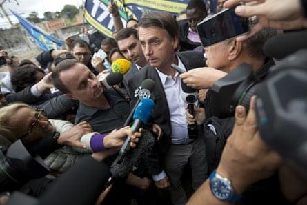 Jair Bolsonaro talks to the press at the Madureira market in Rio de Janeiro on 27 August