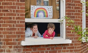 Charlie and Idris look out of a window with a rainbow picture stuck to the glass