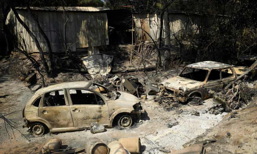 Burnt-out cars outside a house destroyed by the wildfire near the village of Grimaud in Var, southern France
