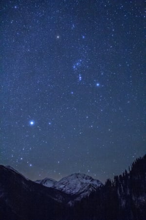The constellations seen here, Orion (the Hunter) and Canis Major (one of the Hunter's hounds) shine bright over Oregon's sixth highest mountain. Sirius, the 'dog star', brightest star in the night sky, can be seen in the upper part of Canis Major