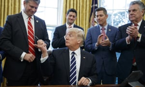 Donald Trump hands a pen to Representative Bill Huizenga after signing House Joint Resolution 41, which lifts rules obliging oil companies to disclose payments to foreign governments.