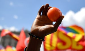 A demonstrator raise a tomato into the air during a march  in protest against the murder of the migrant agricultural worker Soumaila Sacko and the refusal by Italy to except migrants rescued at sea, June 16, 2018, Rome.