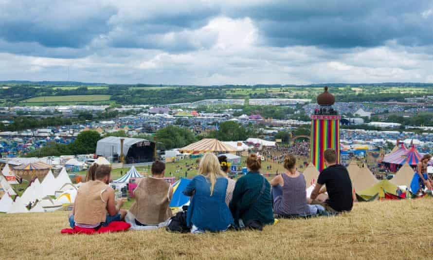 Revellers sit and overlook the festival grounds during Glastonbury 2014.