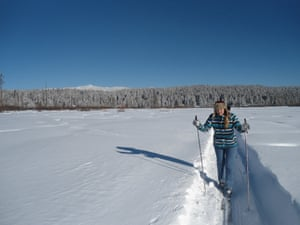 Girl skis through snow trench with ski poles