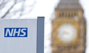 An NHS sign is pictured at St Thomas' Hospital in front of the Big Ben clock face and the Elizabeth Tower