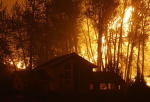 A wildfire burns behind a home on Twisp River Road