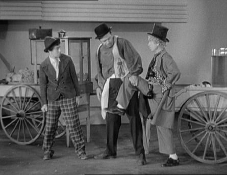 A still from the 1933 film Duck Soup, where Chico and Harpo place their legs into a lemonade stand owner's hands