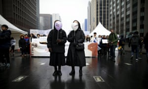 Nuns holding balloons prepare to march during a rally in central Seoul.