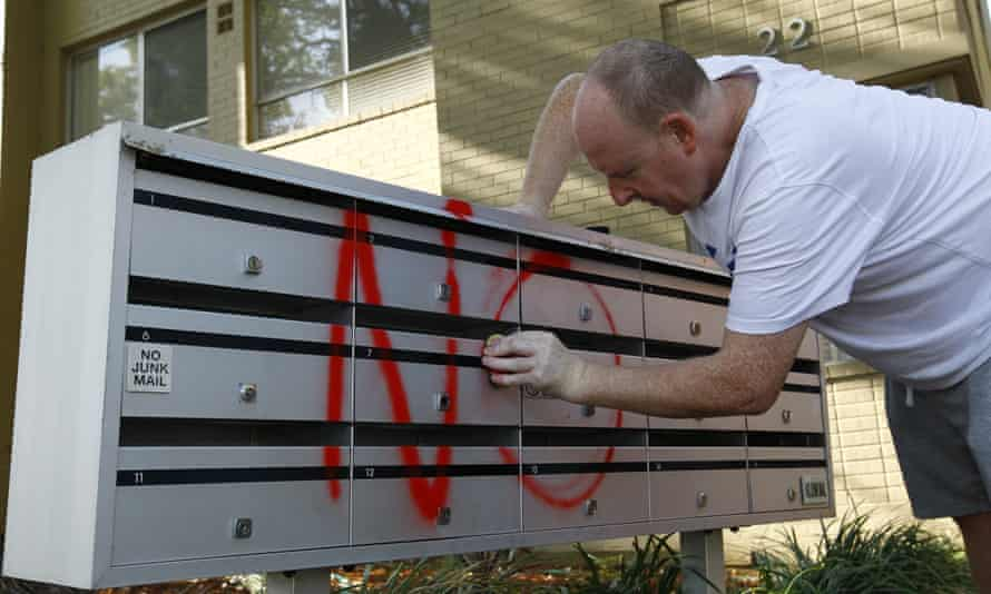 A resident in the Sydney suburb of Stanmore scrubs 'no' graffiti from his letterbox.