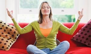 A woman meditating on a sofa