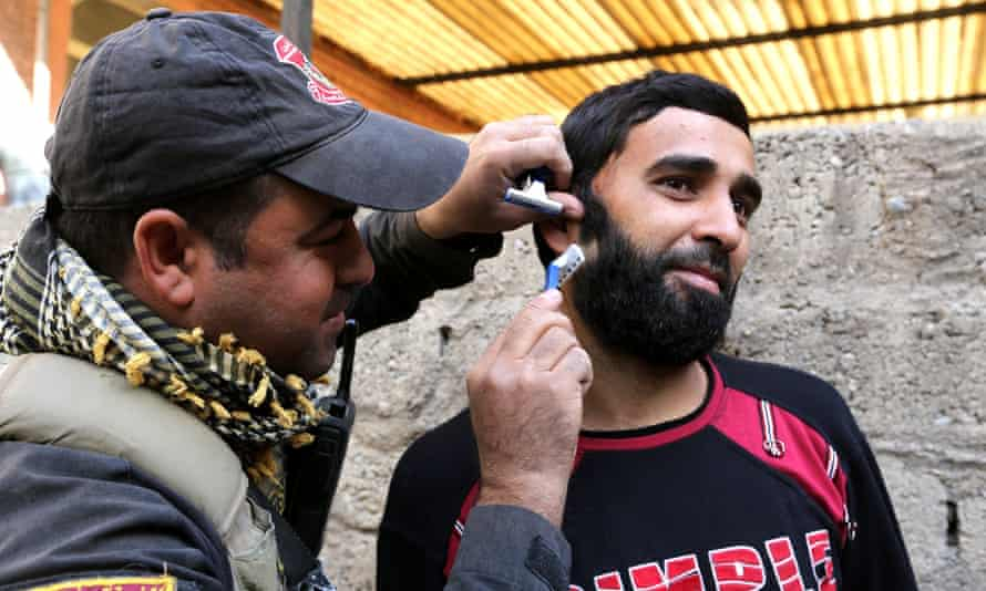 A man has his beard shaved by a special forces soldier in a part of Mosul recaptured from Isis.
