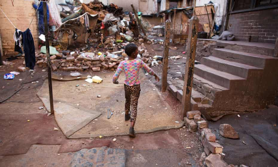A child plays outside the burned-out 54 Soper Road in Johannesburg, where 100 people still live.