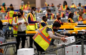 Election workers extract mail-in ballots in a secure room at the Pennsylvania Convention Center in Philadelphia on Tuesday.