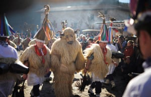 A man dresses in a bear costume during carnival celebrations alongside bell wearing dancers known as Joaldunak during carnival celebrations in Ituren