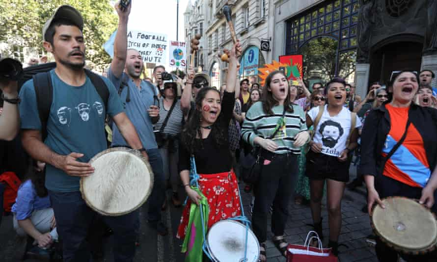 Protesters join a demonstration organised by climate change activists from Extinction Rebellion outside the Brazilian embassy in central London on 23 August.