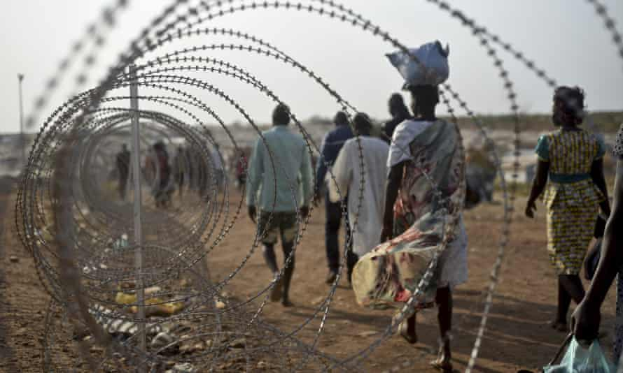 Displaced people walk next to a razor wire fence at the UN base in Juba.