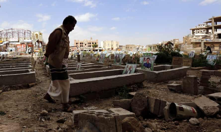 A man walks past graves in Yemen