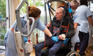 Carers Carol Young and Linda Mckean use a hoist to transfer Eric Johnston, 93, from his wheel chair to a seat in the conservatory