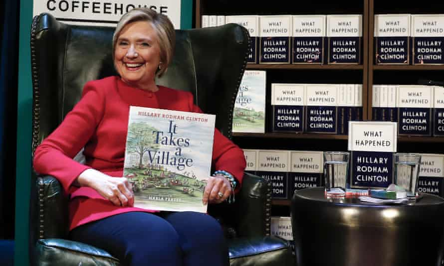 Hillary Clinton, holds her book It Takes A Village as she sits on stage at the Warner Theatre in Washington, Monday, 18 September, during a book tour event for her new book What Happened.