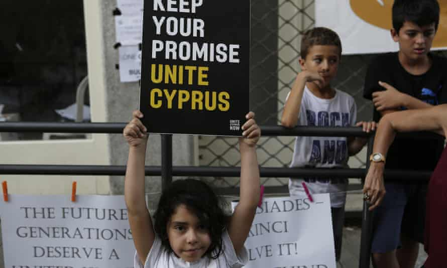 A girl holds up a board during a protest at a crossing point inside the UN buffer zone in Nicosia, Cyprus.