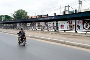 A policeman on a motorcycle passes a deserted bus stop as people remain indoors in compliance with lockdown in Lagos