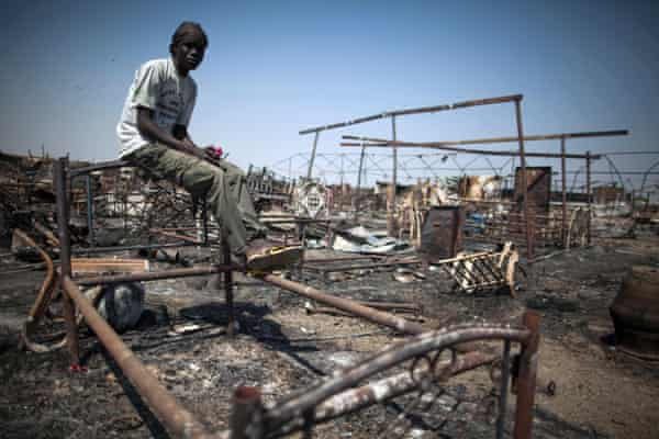 Shaggier Gabriel, a displaced man residing in the United Nations Protection of Civilians (PoC) site in Malakal, South Sudan, sits on his former bed in a burnt and looted area.