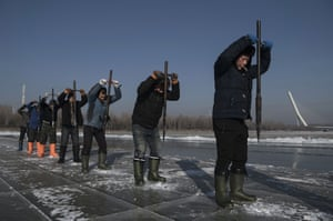 A team of workers use ice picks to dislodge large blocks from the frozen Songhua River