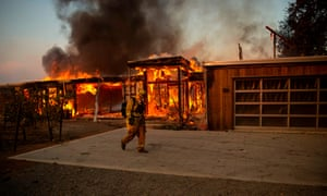A firefighter walks by a house as it burns during the Kincade fire in Healdsburg, California, on Sunday.