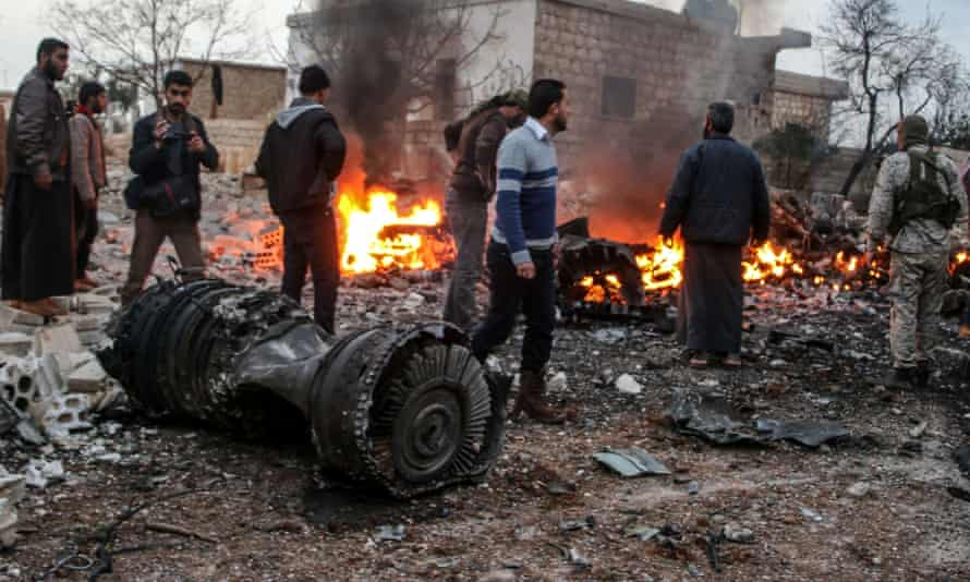 Syrians walk amid the rubble of a Russian fighter jet shot down by rebels in eastern Idlib on 3 February.