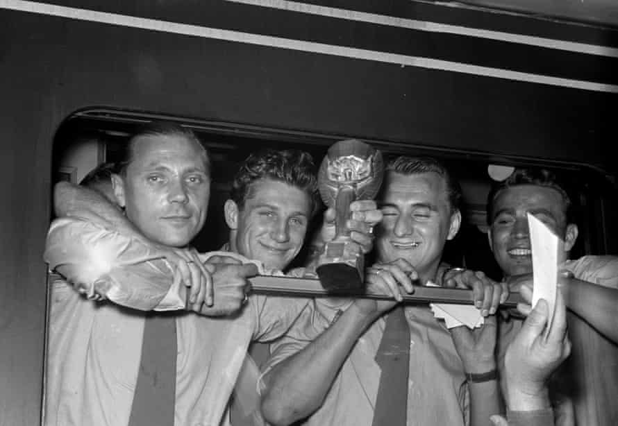 West Germany players – from left: Max Morlock, Hans Schaefer, Jupp Posipal, and Hans Bauer – hold the World Cup trophy during a stop of the train in Singen, Germany a day after the final.