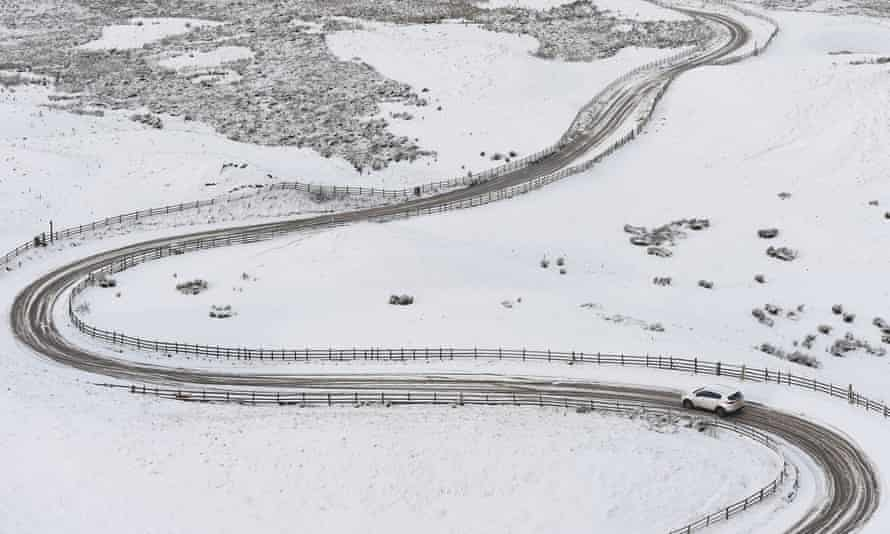 A car makes its way along an icy road near Mam Tor in Derbyshire