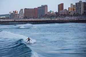 A surfer rides a wave at Durban's North Beach.
