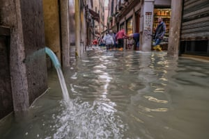 Water is drained from a store by an electric pump in Venice, Italy.