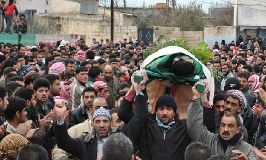 Anti-Syrian regime protesters carry the body of a man during a February 2012 funeral procession in Homs province