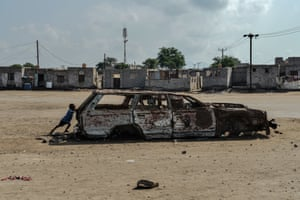 Boy with burned out car in Aden, November 2018