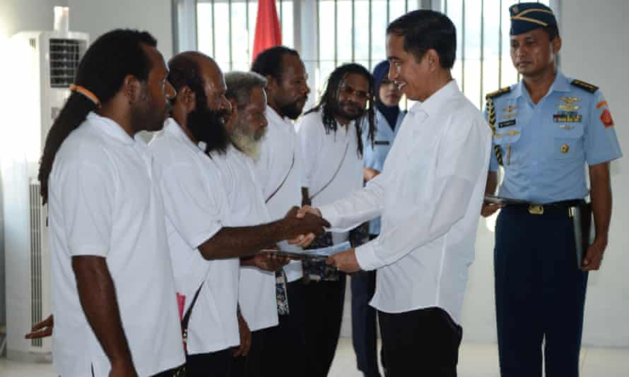 President Joko Widodo shakes hands with freed Papuan political prisoner Kimanus Wenda, second from left, while four others Jefrai Murib, left, Apotnalogolik Lokobal, third from left, Numbungga Telenggen, fourth from left, and Linus Hiluka look on during a ceremony in Abepura prison in Jayapura.
